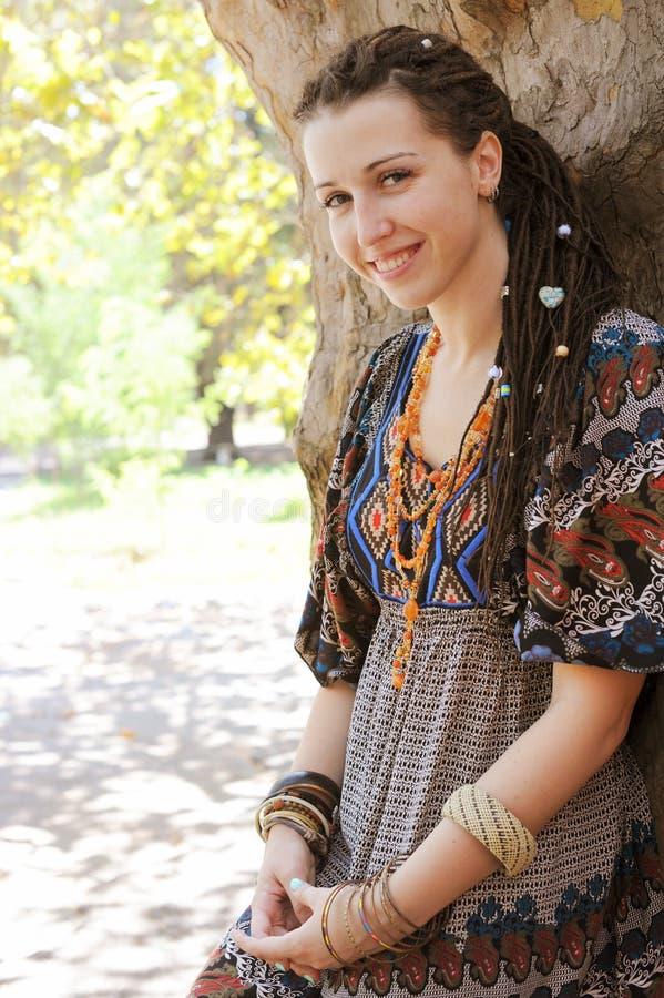 Mujer sonriente linda del estilo del indie del hippie con los dreadlocks, vestidos en la presentación ornamental del vestido del  imágenes de archivo libres de regalías