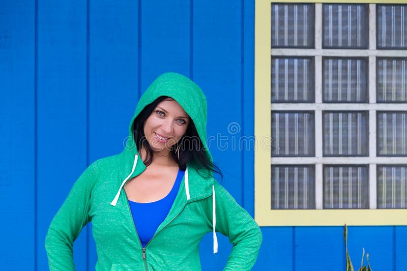 Mujer sonriente linda en una sudadera con capucha verde fotografía de archivo libre de regalías