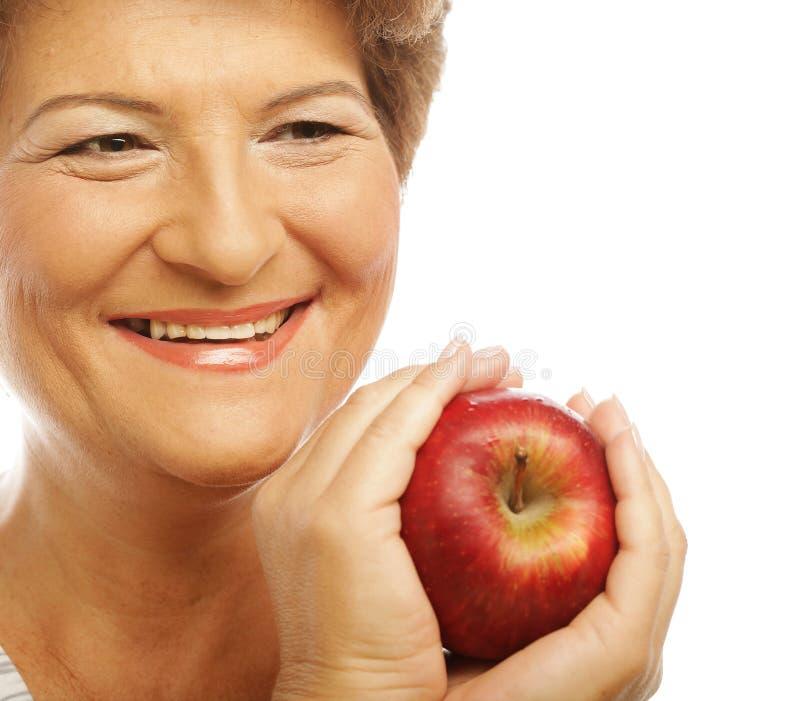 Mujer sonriente madura con la manzana imagen de archivo
