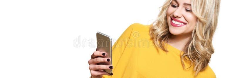Mujer sonriente magnífica que mira su teléfono móvil Mujer que manda un SMS en su teléfono, aislado sobre el fondo blanco foto de archivo libre de regalías