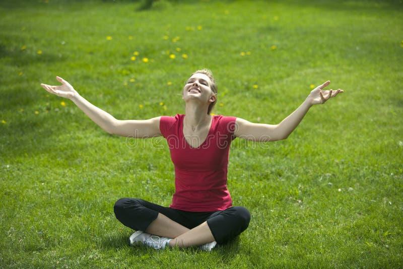 Mujer sonriente meditating imagen de archivo libre de regalías