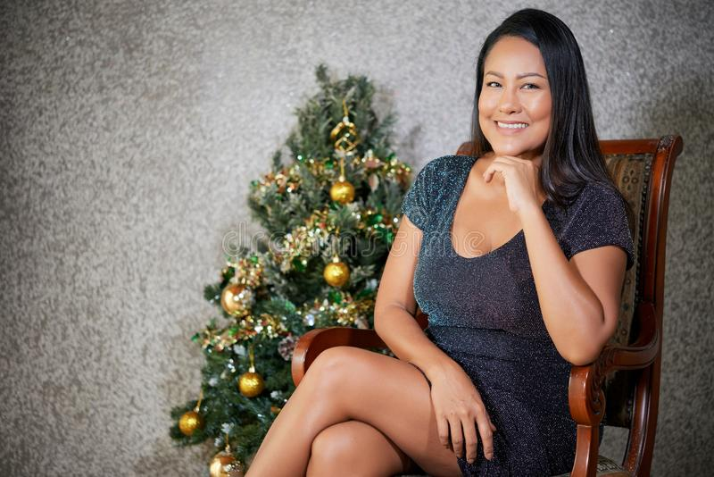 Mujer sonriente moderna en silla cerca del árbol de navidad fotografía de archivo libre de regalías