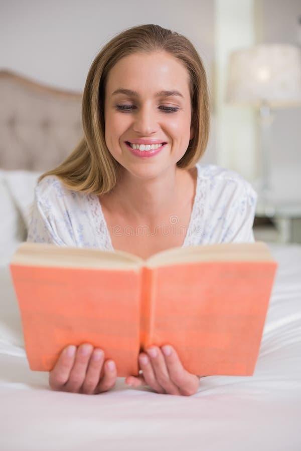 Mujer sonriente natural que miente en la lectura de la cama imagen de archivo