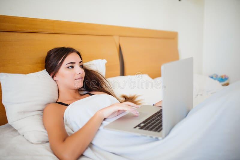 Mujer sonriente que alcanza en sus medios sociales como ella se relaja en cama con un ordenador portátil en un día perezoso fotografía de archivo libre de regalías