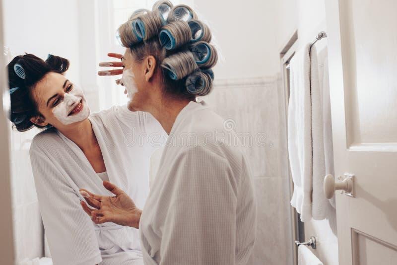 Mujer sonriente que aplica la crema de cara a su madre imagen de archivo libre de regalías