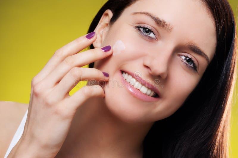 Mujer sonriente que aplica la crema hidratante fotos de archivo libres de regalías