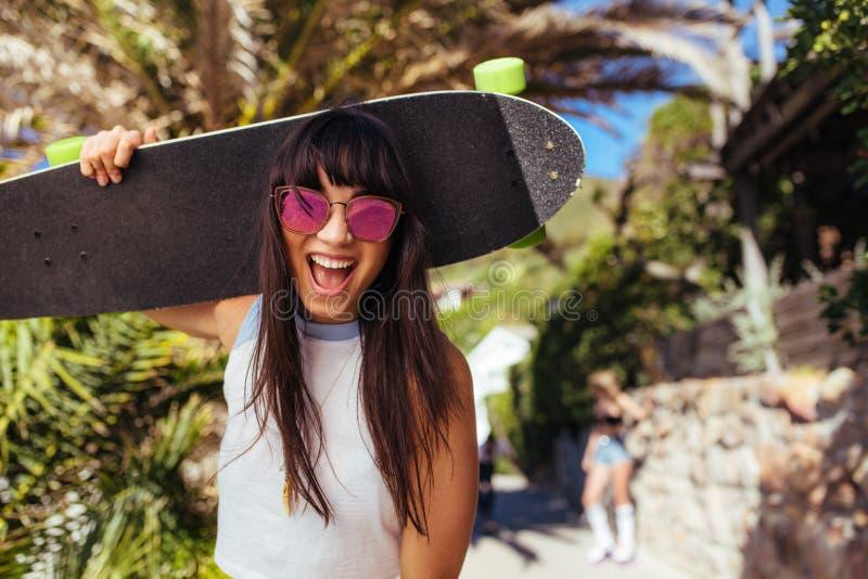 Mujer sonriente que camina al aire libre sosteniendo el monopatín imagenes de archivo