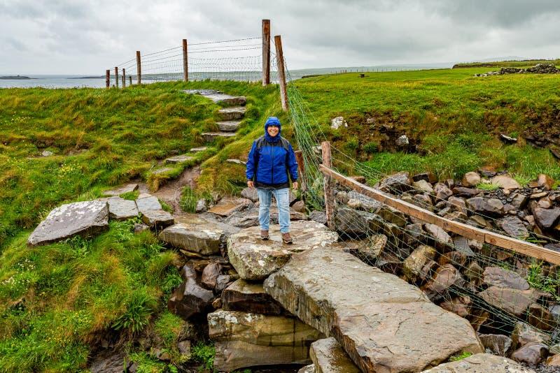Mujer sonriente que camina en un puente de piedra en la ruta costera del paseo de Doolin a los acantilados de Moher fotos de archivo