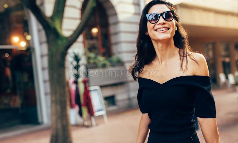 Mujer sonriente que camina a lo largo del camino en ciudad imagenes de archivo