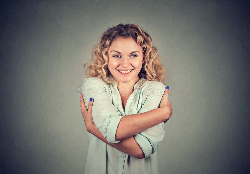 Mujer sonriente que celebra el abrazo Concepto del amor usted mismo fotos de archivo