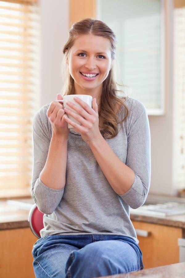 Mujer sonriente que come una taza de café en la cocina foto de archivo