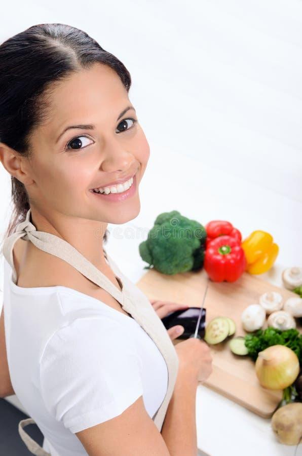 Mujer sonriente que corta verduras en una cocina fotos de archivo
