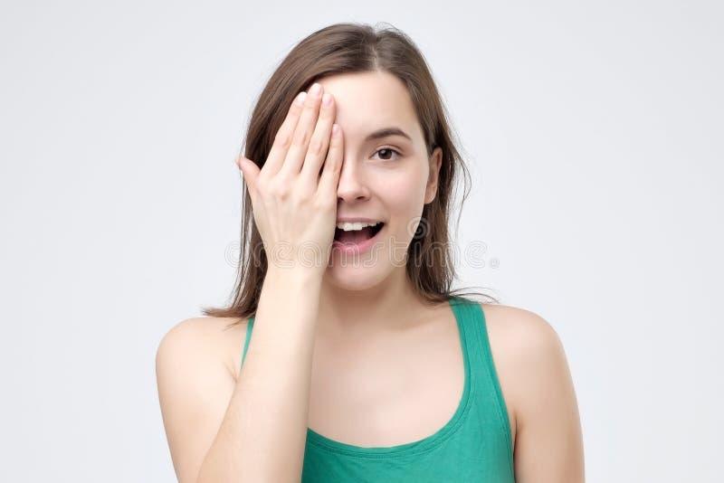 Mujer sonriente que cubre un ojo con su mano como ella se coloca de mirada de la cámara imagenes de archivo