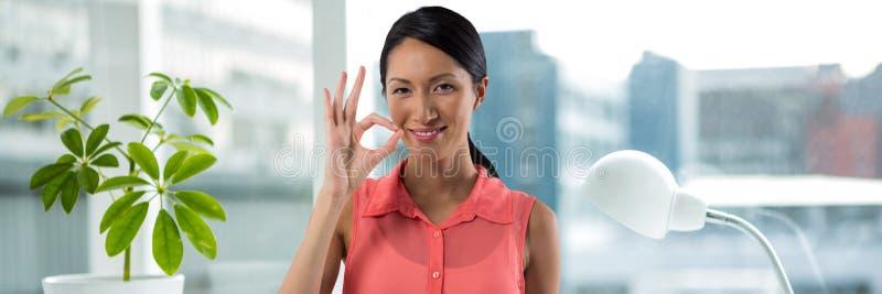 Mujer sonriente que da el O muestra de k foto de archivo