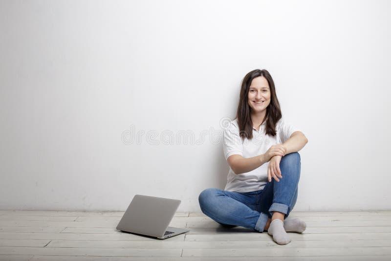 Mujer sonriente que descansa de la sentada feliz del trabajo por la pared en fotografía de archivo libre de regalías