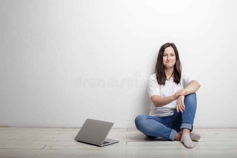 Mujer sonriente que descansa de la sentada feliz del trabajo por la pared en fotos de archivo libres de regalías