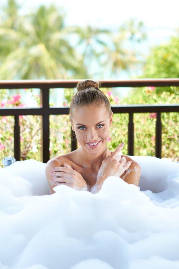 Mujer sonriente que disfruta de un baño de burbujas relajante imágenes de archivo libres de regalías