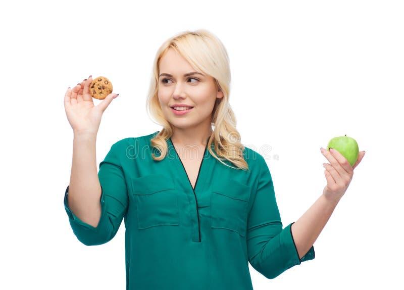 Mujer sonriente que elige entre la manzana y la galleta foto de archivo