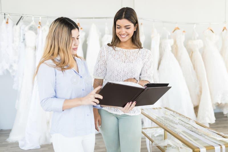 Mujer sonriente que elige su vestido de boda de catálogo en tienda foto de archivo libre de regalías