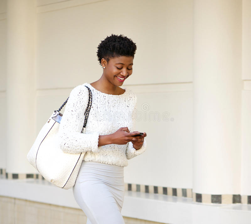Mujer sonriente que envía el mensaje de texto en el teléfono móvil imagen de archivo libre de regalías