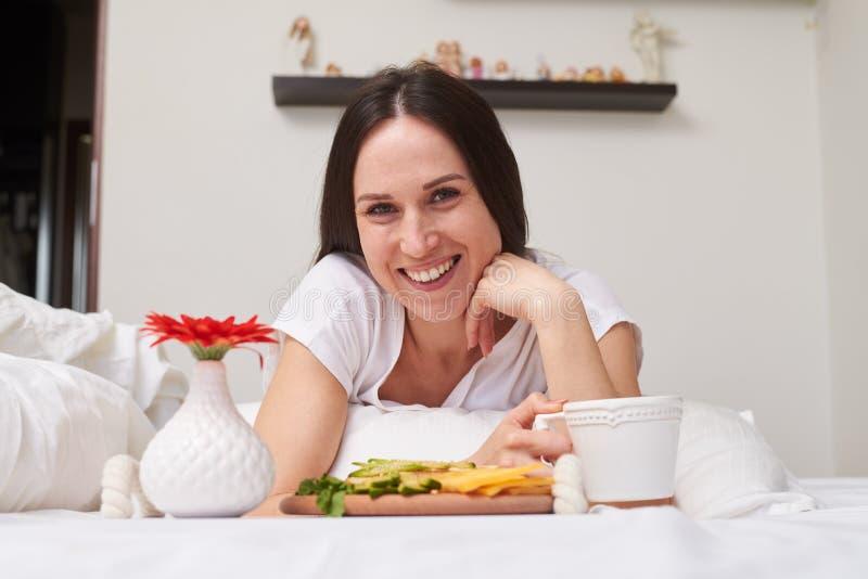 Mujer sonriente que es satisfecha con el desayuno imágenes de archivo libres de regalías