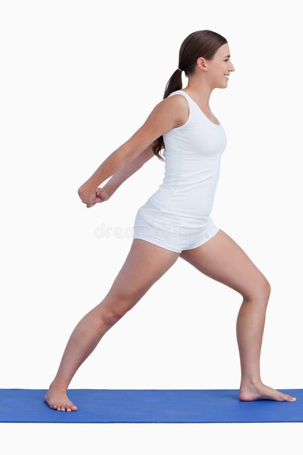 Mujer sonriente que estira sus brazos mientras que se coloca vertical imagen de archivo