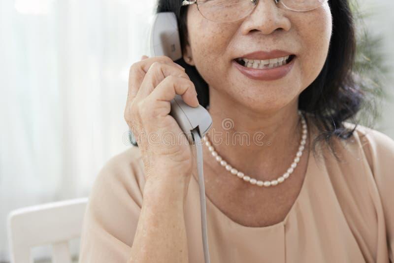 Mujer sonriente que habla en el teléfono fotografía de archivo libre de regalías