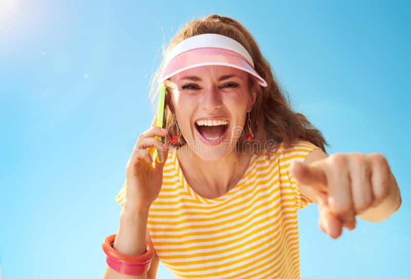 Mujer sonriente que habla en el teléfono celular y que señala in camera fotos de archivo