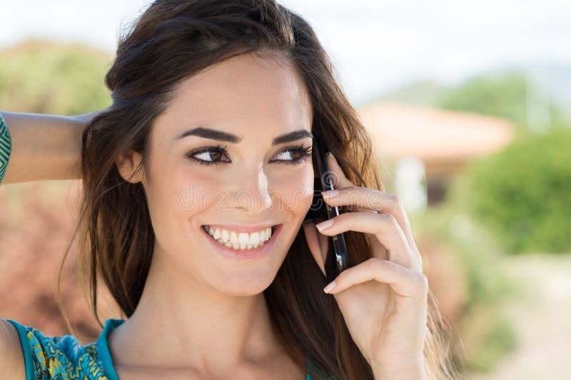 Mujer sonriente que habla en el teléfono móvil fotografía de archivo libre de regalías