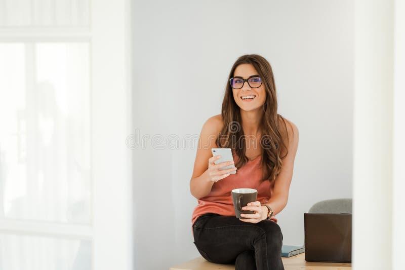 Mujer sonriente que habla en el teléfono que toma un descanso para tomar café imagen de archivo libre de regalías