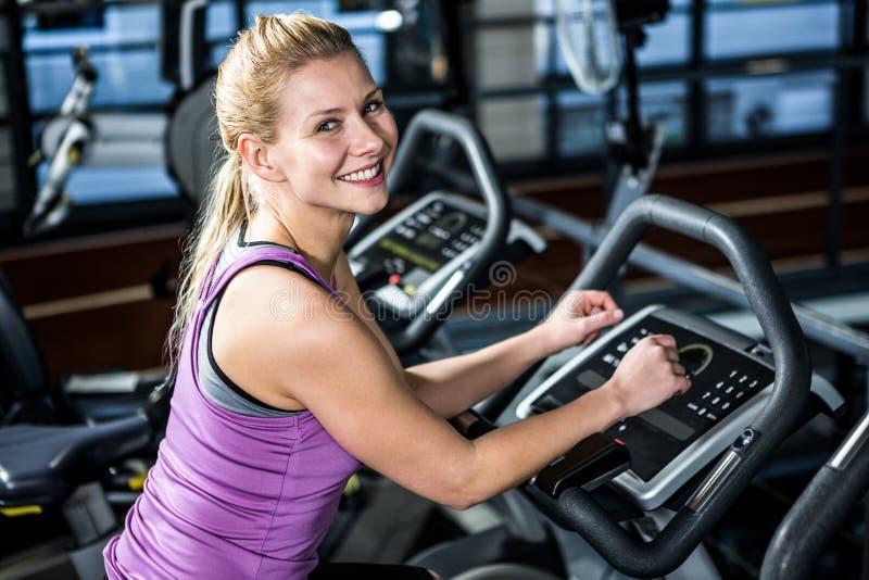 Mujer sonriente que hace ejercicio de la bici fotos de archivo