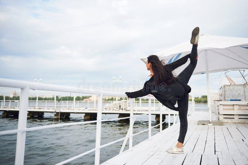 Mujer sonriente que hace ejercicio de la yoga al aire libre en el embarcadero de la playa imágenes de archivo libres de regalías