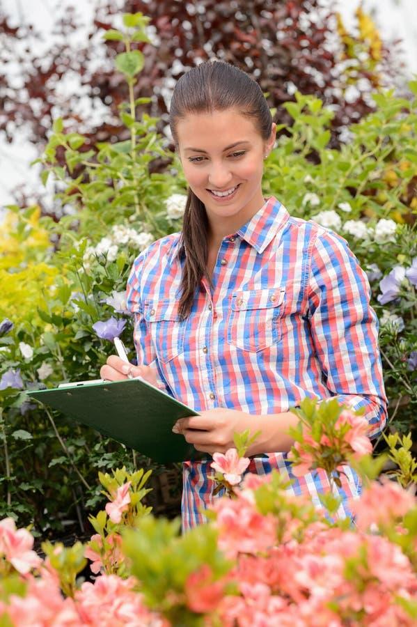 Mujer sonriente que hace inventario en el centro de jardinería imagenes de archivo