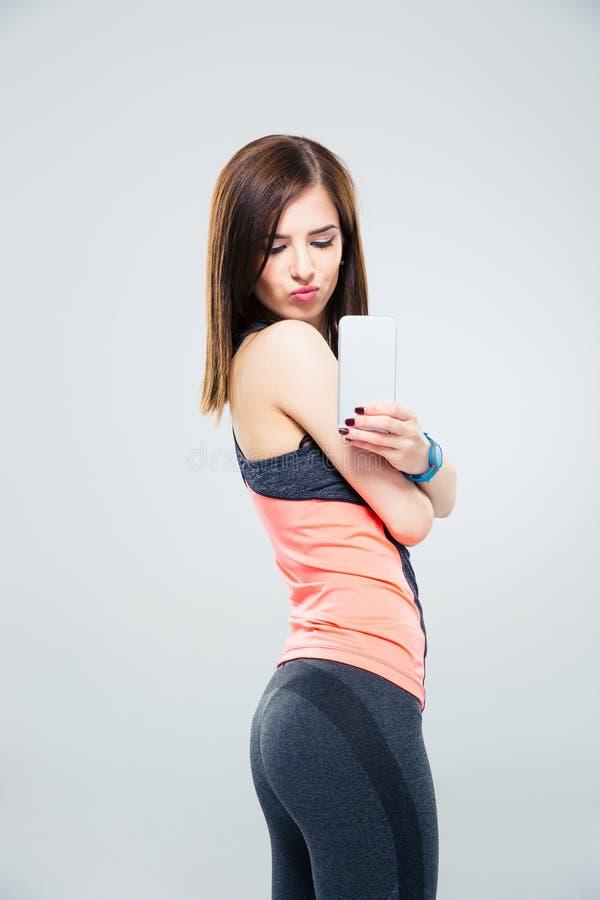 Mujer sonriente que hace la foto en smartphone imagen de archivo libre de regalías