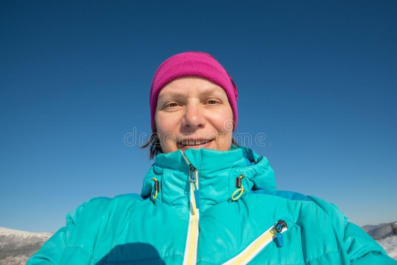 Mujer sonriente que hace una foto de sí mismo en un día de invierno soleado adentro foto de archivo