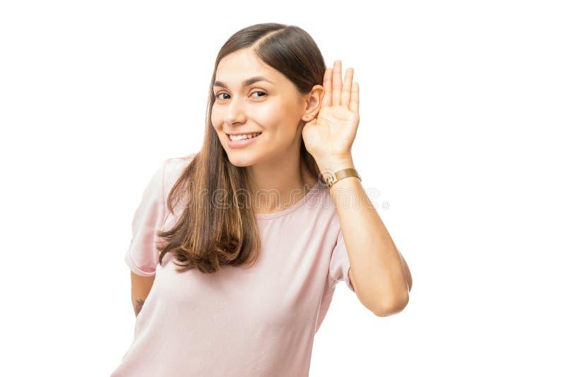 Mujer sonriente que intenta escuchar algo foto de archivo libre de regalías