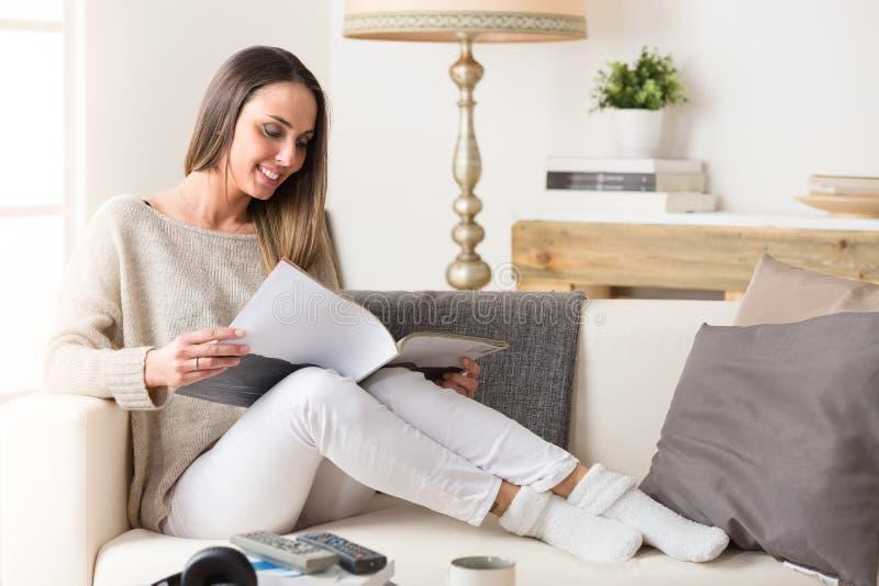 Mujer sonriente que lee una revista en un sofá fotografía de archivo libre de regalías