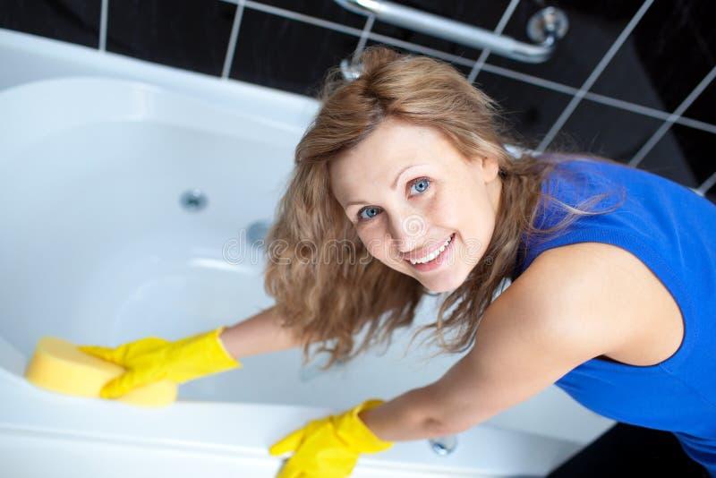 Mujer sonriente que limpia un baño fotografía de archivo