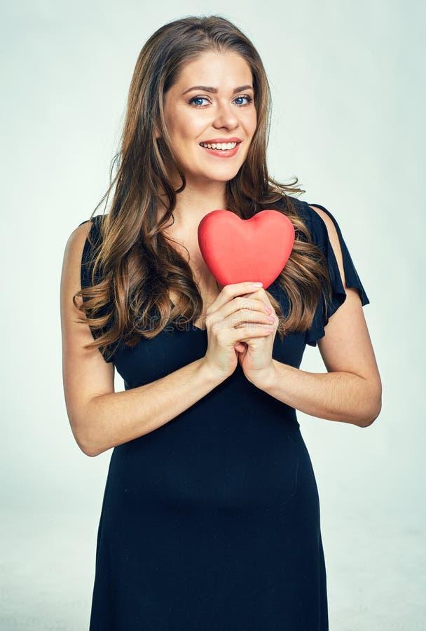 Mujer sonriente que lleva el vestido negro que lleva a cabo el corazón rojo foto de archivo