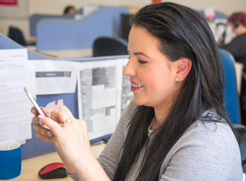 Mujer sonriente que manda un SMS en el teléfono móvil en el trabajo foto de archivo