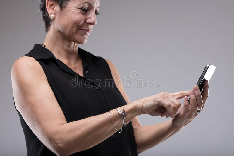 Mujer sonriente que mecanografía un mensaje de texto foto de archivo