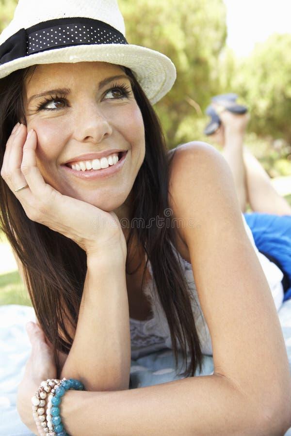 Mujer sonriente que miente en la hierba que lleva el sombrero de Sun foto de archivo