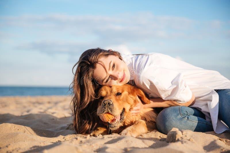 Mujer sonriente que miente y que abraza un perro en la playa foto de archivo libre de regalías