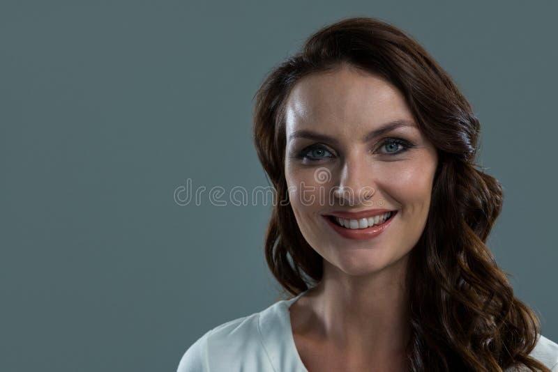 Mujer sonriente que mira la cámara contra fondo gris imagen de archivo libre de regalías