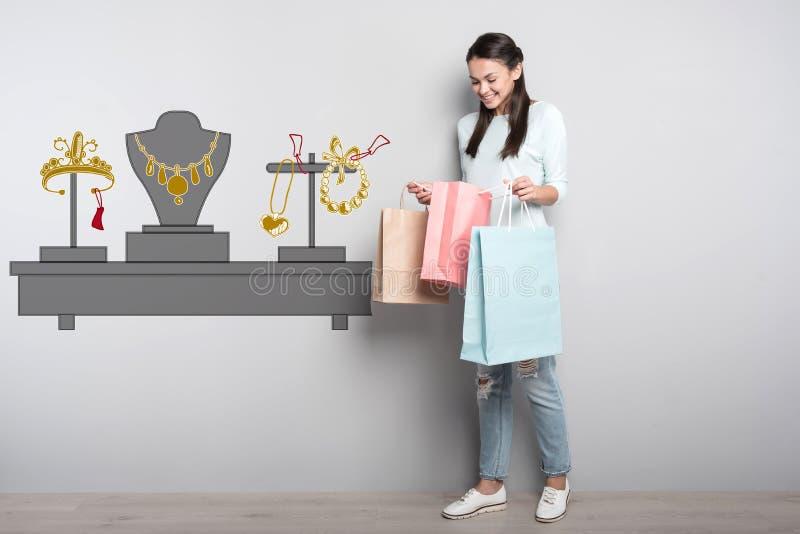 Mujer sonriente que mira su compra mientras que estando en una tienda fotos de archivo