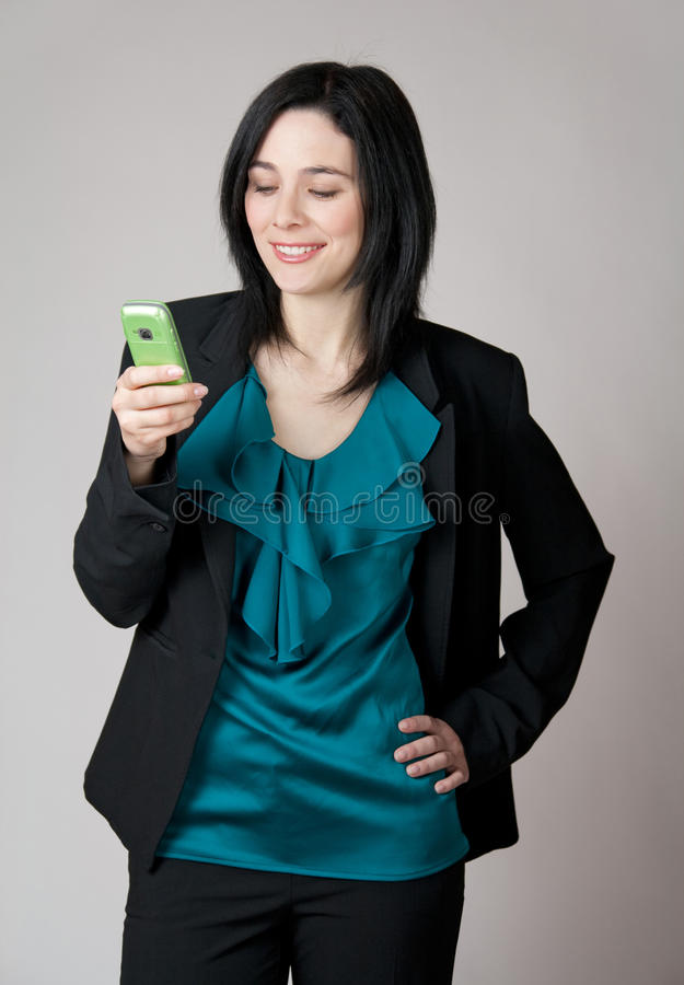 Mujer sonriente que mira su teléfono celular fotos de archivo