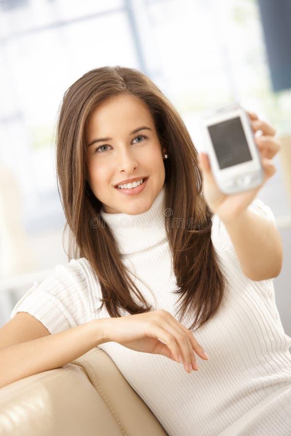 Mujer sonriente que muestra el teléfono móvil fotos de archivo libres de regalías