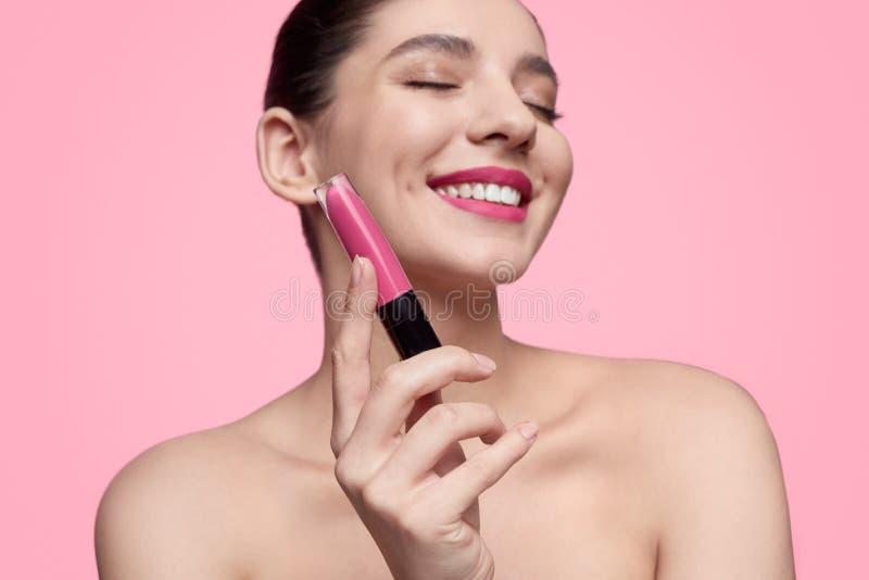 Mujer sonriente que muestra la barra de labios líquida foto de archivo