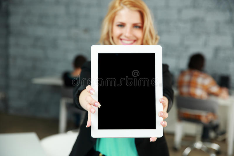Mujer sonriente que muestra la pantalla de tableta en blanco fotografía de archivo