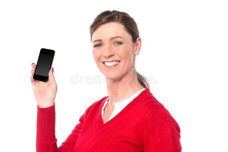 Mujer sonriente que muestra un teléfono elegante imagen de archivo